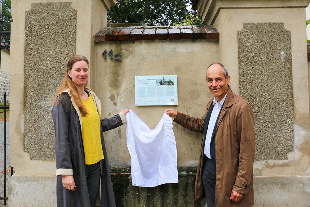 Pfarrerin G. Zachow und Ortsvorsteher W. Sträter (v.l.) bei der Enthüllung des Fontane-Schildes am Eingang der Groß Gienicker Dorfkirche