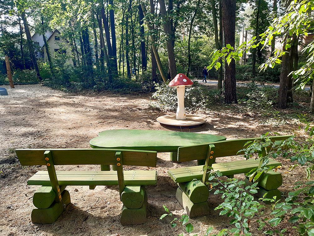 Ein Pilzrondell (mit Bezug auf den Straßennamen), eine grüne Sitzgruppe mit einem Tisch in Blattform
