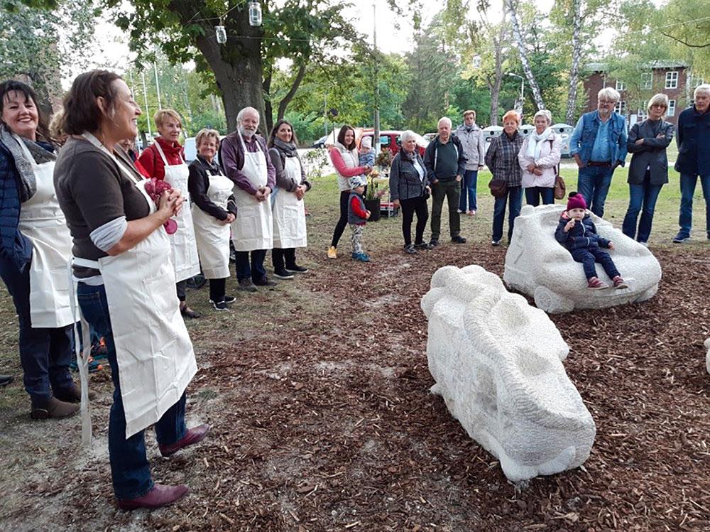 Birgit Cauer (vorne) präsentiert mit den BildhauerInnen die fertigen Werke in Groß Glienicke