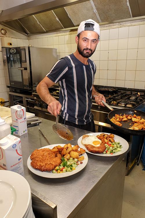 """Das """"Schlossschitzel"""" (vorn), eine Eigenkreation des Krugs, hat Talha Khalid mit knusprigen Cornflakes paniert"""