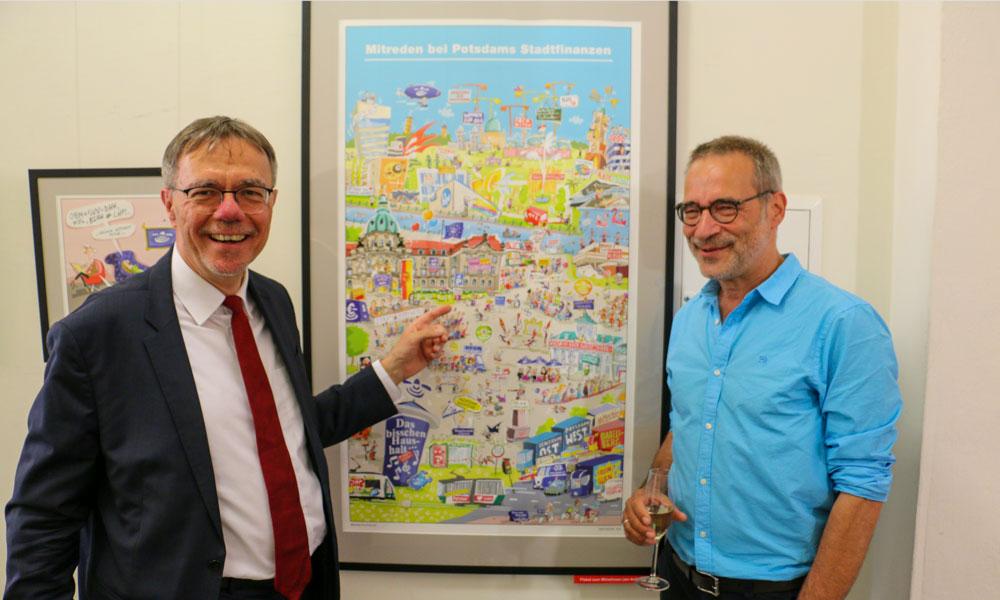 Der Beigeordnete für Finanzen der Landeshauptstadt Potsdam, Burkhard Exner (l.) hat auch sich auf dem Wimmelbild von Jörg Hafemeister (r.) gefunden