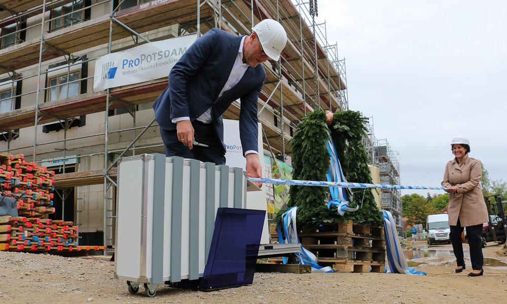 Wieder über 150 Wohnungen gebaut. Bert Nicke und Brigitte Meier beim Abschneiden des Zählbandes, das den Stand der gebauten Wohnungen anzeigt.