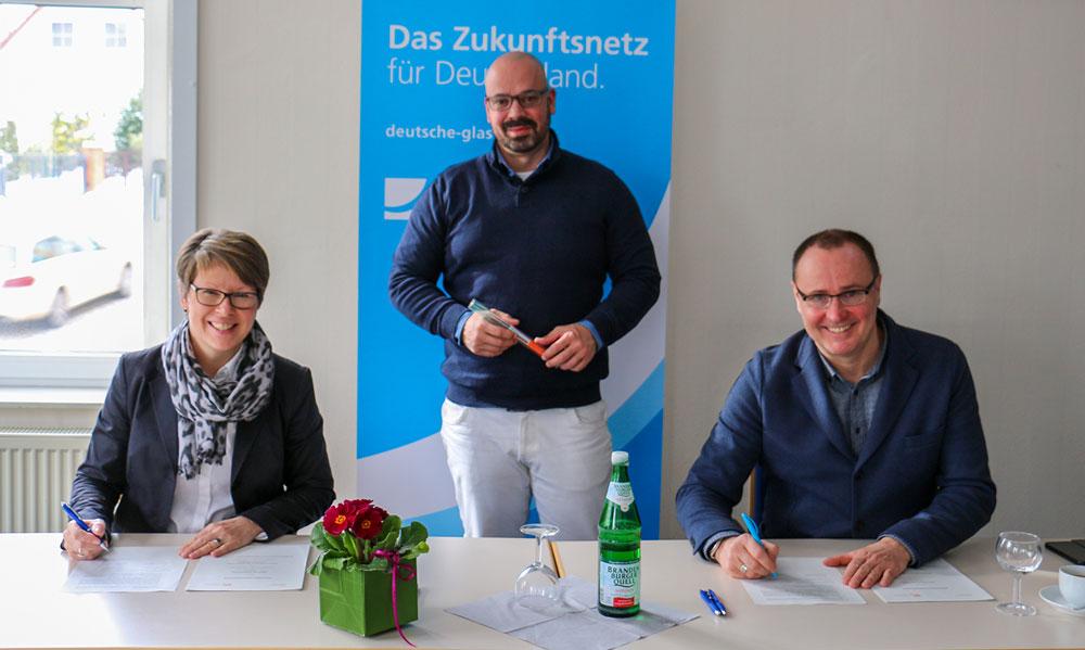 Bürgermeisterin Kerstin Hoppe (l.) und Michael Kölling von der Deutsche Glasfaser (r.) unterzeichnen den Kooperationsvertrag, Vertriebsleiter Maik Zappe in der Mitte