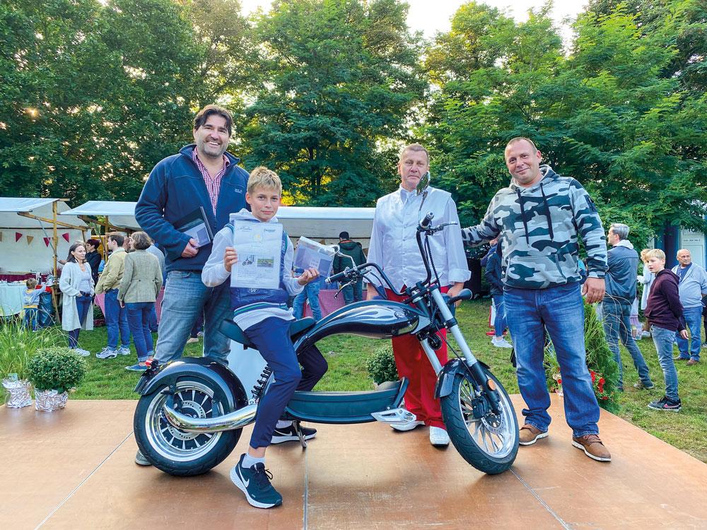 Die beiden Gewinner der Hauptpreise: Michael Oppel (l.) und Christopher Wolf auf seinem neuen E-Chopper, daneben Matthias Völker (Moderator und Mitorganisator des Festes) und Robert Clasen von der Firma E-Choppper Berlin-Brandenburg